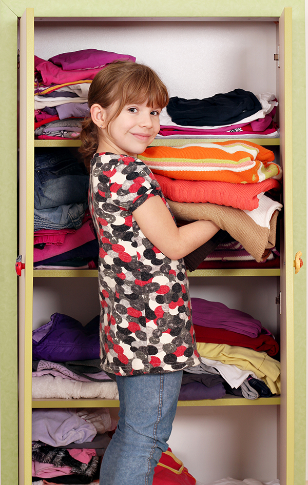 little girl girl agrees clothes in a closet